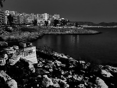 Ruins of ancient walls_IMG_6143n (AchillWandering) Tags: blackandwhite ancient history night water black white downtown archaeological walls ruins sea piraeus coast greece conon athens athenians longwalls themistoclean road pavement strolling rocks