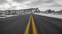 Badlands Loop Road (Paul Domsten) Tags: road mountain sky landscape pentax badlands badlandslooproad snow winter southdakota wall skull peaks clouds nationalpark artistic fossil trail monochrome black white fossilexhibittrail yellow lines fineart selectivecolor