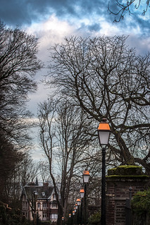 lamp posts lead the eye to a mansion in the trees under a stormy sky, Honfleur, Calvados, Normandy, France