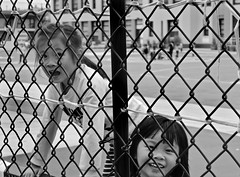 Noriega Preschool - San Francisco, CA (Rex Mandel) Tags: children girls kids blackandwhite bw sanfrancisco sf preschool smiling curious fence monochrome outdoors schoolplayground street streetphotography portrait streetportraits