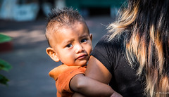 2017 - Mexico - Zihuatanejo - Market Day - 2 of 2 (Ted's photos - For Me & You) Tags: 2017 cropped mexico nikon nikond750 nikonfx tedmcgrath tedsphotos tedsphotosmexico vignetting zihuatanejo zihuatanejoguerrero zihuatanejomexico baby candid portrait hair bokeh child ear lips eyes orange