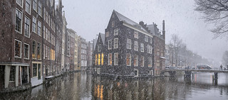 Snowflakes falling on the most idyllic and oldest canals of Amsterdam