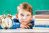 Small boy sitting with alarm clock near blackboard (evolutionlabs) Tags: chalkboard student school exam alarm child alarmclock blackboard blond books boy caucasian class pupil smart clock educational schoolchild intelligent woken desk education schoolboy eyes face homework kid learning lesson library lying one people person shock shocked smiling stack studying stylish wakeup background classroom portrait study board primary little looking ukraine