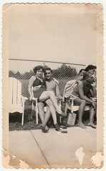Vintage 1950s Snapshot : LapLounger Couple Chilling Poolside (CHAIN12) Tags: scan photo vintage girl woman younglady swimsuit hlncr1950spoolsidelapsitcouple shirtless boy loafers chainlink fence chair