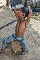 The young son's job (Pejasar) Tags: family business sugarcane processing near delhi india hoe stir thickening sugar raw candy brown work later stage boy shirtless child resting bored watching seated barefoot son