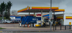 Fill Me Up Before You Fill Me Up (M C Smith) Tags: refuse truck petrol diesel pumps pentax k3 lamps pavement kerb signs letters numbers symbols car cars parking crossing lights name streetname blue orange yellow white black clouds trees green speakers canopy