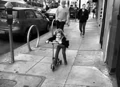 Polk Street, Tenderloin - San Francisco, CA (Rex Mandel) Tags: child girl motionblur girlandparents sanfrancisco sf tenderloin polkstreet street girlonarazer joy blackandwhite bw sidewalk streetphotography littlegirlplaying