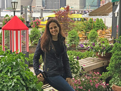 Sitting on a Bench in a Pretty New York Setting (soniaadammurray - Off) Tags: iphone newyork usa park trees flowers people water watertaxi architecture river restaurant awning tables chairs family beauty woman fences bench benchmonday