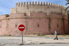 Modern Life in Historic City (Alex L'aventurier,) Tags: maroc morocco essaouira mogador sign woman femme candid street rue rampart wall mur sky ciel fortress forteresse architecture palmtree palmier old vieux historic historique historical cellphone