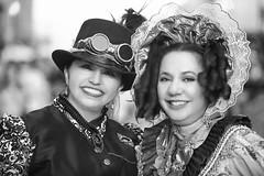 Sisters (wyojones) Tags: texas galveston dickensonthestrand holidayfestival hat blackandwhite dress steampunk goggles gears hair redhair brunette lady lovely woman beautiful beauty feathers smile pretty curls browneyes bonnet earrings greyscale bw monochromatic