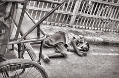 Life on the edge (Pejasar) Tags: man asleep edge road street busy delhi india cart wheel blackandwhite bw barefoot