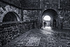 Stirling Castle Entrance (Geoffrey Tibbenham) Tags: stirlingcastle scotland stone arch light human silhouette blackandwhite outdoor street structure monochrome fuji xt1 12mm ziess touit leading lines pavement
