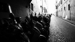 Urban transport (halifaxlight) Tags: italy tuscany florence mopeds parking street cobblestones figures buildings transport bw bokeh scooters