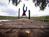 Man standing on hands on a pier in the fall (ivan_volchek) Tags: wood outdoors water nature sky tree wooden landscape travel traveling visiting go summer people park daylight leisure environment log lake handstand force pier