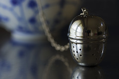 The art of tea making (alideniese) Tags: smileonsaturday shinymetals metal closeup bokeh reflection teainfuser infuser cup chain stainlesssteel shiny bright light shadow dark steeltable alideniese antiquecup oldcup blueandwhite china crockery stilllife classic rounded holes perforated art artistic daylight vintage teaforone timefortea solitary cafe
