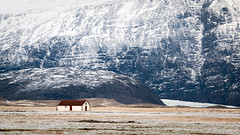 the Farmhouse (Brady Baker) Tags: iceland europe adventure travel farmhouse scale building landscape mountain plain agriculture cold climate winter snow ice soft color red expansive