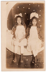 Vintage Photo Postcard circa 1910 : Portrait of 2 Sisters Seated on Moon Backdrop (CHAIN12) Tags: postcard rppc photo girls 2 sister sisters darkhair arcade souvenir papermoon bow hair seated pprmnmncirca1910rppc2girlspapermoonportrait moon studio portrait stars twin twins