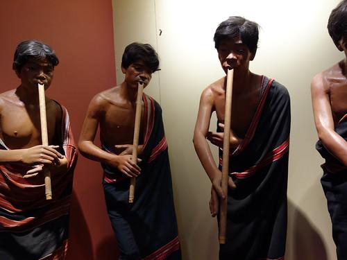 Des statues d'hommes bahnars jouant d'un instrument en bambou