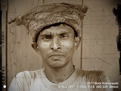 2017-09a India's Northeast (37) (Matt Hahnewald) Tags: matthahnewaldphotography facingtheworld character head face eyes consent rapport travel culture lifestyle market bazaar roadside porter bearer carrier labourer mono monochrome sepia antiqued vignette silchar assam india asia asian indian oneperson male adult man picture photo faceperception physiognomy nikond3100 primelens 50mm 4x3 horizontal street portrait closeup hat outdoor editing posing authentic manly fatakbazar northeast postprocessing fullfaceview expression headshot middleaged nikkorafs50mmf18g lookingcamera