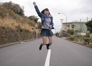 High school girl jumping on street near school