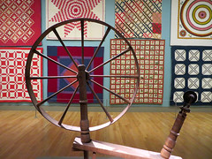 Quilts seen through a spinning wheel. (vickilw) Tags: thehuntington quilts spinningwheel spokes wood 812018 81118 7dos sunday geometry wheels