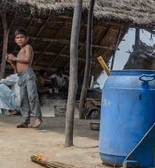 barn dancing? (Pejasar) Tags: family business sugarcane processing near delhi india home work boy child pants torn back shirtless onefoot dance bluebarrel broom barefoot