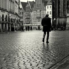 Münster today (Bernhardt Franz) Tags: münster today heute kopfsteinpflaster cobblestone man people menschen church buildings facades prinzipalmarkt lambertikirche wet nass regnerisch blackandwhite bw street