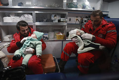 Syrian paramedics distract children inside an ambulance on the second night of an evacuation operation led by the Syrian Red Crescent and the International Committee of the Red Cross in Douma in the eastern Ghouta region on the outskirts of the capital Da