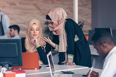 Two woman with hijab working on laptop in office. (Unctad_DTL) Tags: hijab laptop woman work office group people muslim corporate business adult computer female happy modern professional worker arab saudi arabian businesswoman arabic beautiful confident portrait pretty white young women girl student attractive background education ethnic lady smile university male meeting plan success table talking teamwork technology busy beard bright businessman bosniaandherzegovina