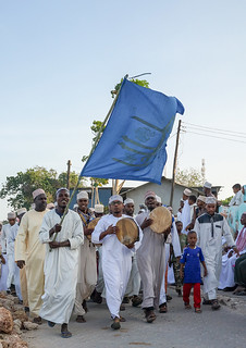 Sunni muslim people parading with flags during the Maulidi festivities in the street, Lamu County, Lamu Town, Kenya