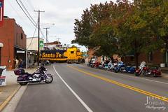 New Bikes, Old Locomotive (jwjordak) Tags: 2546 trees motorcycle people gradecrossing crossbuck fallcolor atsf cf7 store street train newhaven kentucky unitedstates us