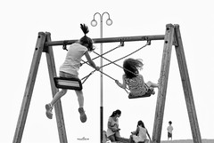 swings (dim.pagiantzas | photography) Tags: swings street people kids woman female male boys girls environment entertainment lights playground grayscale monochrome blackandwhite motion outdoor teens
