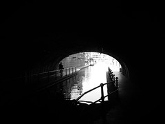 out of darkness (vfrgk) Tags: dark light lightandshadows humanfigures walking waterreflections undulation tunnel darkmood candidstreet streetphotography streetscene streetlife streetsnap urbanphotography urbanfragment urbanlife monochrome blackandwhite bw bnw canal canalboats lowlight stroller silhouette people moody atmospheric
