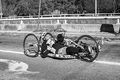 Wheelchair Athlete (burnt dirt) Tags: wheelchair bicycle bike athlete competition helmet uniform marathon halfmarathon 5k course race racer pedal wheel flag road street amputee prosthetic sunglasses glasses downtown town city bw blackandwhite fujifilm camera metro station busstation trainstation hero military xt1 streetphotography urban candid portrait documentary laugh smile winner medal sport vehicle outdoor people person abb5k houston texas houstonmarathon houstonhalfmarathon chevron man woman crank gloves sunny cold camelbaktopend