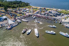 Aerial view festival as crowd gathers along dockside while various boats float anchored near by, Deal Island, Maryland. (Remsberg Photos) Tags: boat maryland sailing seafood skipjack waterman vessel watervessel easternshore chespeakebay outdoors watermen dealisland coastline leisureactivity bayofwater boatdocking dock competition fastpaced sport competitive race aerial viewfromabove drone crowd audience spectacle bleachers motorboat summertime summer moored anchor cars usa