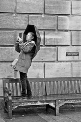 Too wet to sit (sasastro) Tags: streetphotography snapper umbrella rain candid urban cambridgeuk bench