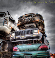 A Stack of Scrap Cars (SoS) (13skies) Tags: smileonsaturday cars scrap junkyard parts pieces selling money old rusted scapyard junk lights doors older accidents mishaps crashes grills fixing repair mechanics canont3i hdr skies grey clouds highdynamicrange stacked
