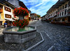 Flowers in Gruyeres, Switzerland (` Toshio ') Tags: toshio gruyeres switzerland swiss swissalps europe european street fountain flowers city cobblestone sky fujiex2 ex2