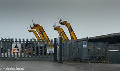 Pointing Skywards (M C Smith) Tags: yellow gates fences grey posts forklifts truck trailer road tarmac wiremesh locked sky letters symbols car buildings industrial