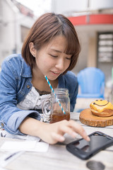 Young woman typing message on smartphone at open cafe (Apricot Cafe) Tags: img36987 asia asianandindianethnicities cafe japan japaneseethnicity shibuyaward sigma35mmf14dghsmart tokyojapan beautifulwoman blackhair brownhair buildingexterior candid carefree casualclothing charming cheerful citylife colorimage communication connection day doughnut enjoyment foodanddrink friendship glass happiness harajukudistrict icecoffee leisureactivity lifestyles lunch oneperson onlyjapanese onlywomen onlyyoungwomen outdoors people photography restaurant shopping sitting smartphone smiling student sunlight table typing waistup women youngadult