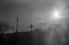 Man Stretching, Sunset Park, Brooklyn (josephkrings) Tags: 1stavenue brooklyn greenwoodcemetery ilfordhp5 newyork nikkor28105mm13545 nikonn70 sunsetpark blackandwhite excercise park silhouette