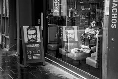beeing watched (nancy_rass) Tags: advertisement banner man woman reflection window cafe eating restaurant street grayscale monochrome