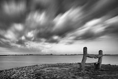 Lonely bench (Martijn Nijenhuis) Tags: roegwold water bench bank clouds wolken lange opname zwart wit black white stenen rocks pebbles dannemeer gemeente slochteren midden groningen staatsbosbeheer
