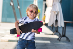 Adorable kid outdoors. Cute pretty child in sunglasses smiling at camera. Casual boy on summer time skating on a skateboard. (elenachukhil) Tags: boy child kid skateboard skate outdoors emotional pretty little cute son havingfun outside strippedshirt sunglasses summer spring happy happiness childhood adorable very blond longhair human people spendingtime leisure joy male jeans hobby expression fun youth sport roller smile enjoy ride person white skater cheerful caucasian active