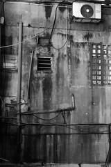wall (k0syak) Tags: sonyilce6000 sonya6000 sigma30mmf14dcdncontemporary haifa israel bwblackandwhite geometry urban wall window brick pipe aircondition bars decay stain concrete pattern lowlight night dark cable