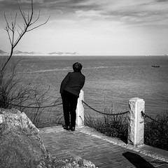 Thoughts drowned in the sea (Go-tea 郭天) Tags: yantaishi shandongsheng chine cn yantai sea side water front horizon far clouds sky rocks chain trees boats waves woman old lady back backside candid lost thinking thoughts cold winter day sun sunny shadow landscape alone lonely street urban city outside outdoor people bw bnw black white blackwhite blackandwhite monochrome naturallight natural light asia asian china chinese shandong canon eos 100d 24mm prime