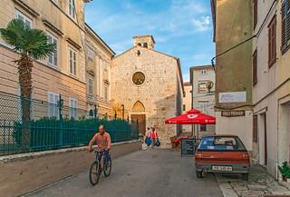 Cyclist on Marta Str with old Franciscan Church
