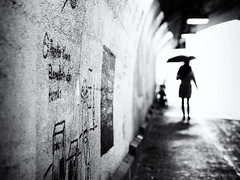 lady with umbrella (Sandy...J) Tags: olympus atmosphere alone atmosphäre walking walk white women wall wand urban underpass unterführung umbrella blackwhite bw black light licht street streetphotography sw schwarzweis strasenfotografie stadt silhouette germany grafitti gegenlicht backlight monochrom deutschland noir tunnel blur blurred city contrast regenschirm