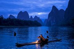 Lijiang's Repose (Hilton Chen) Tags: cormorantfisherman xingpingfishingvillage landscape peaceful dawn birds china guangxiprovince bluehour bambooraft serene pipe smoking guilin karstmountains jaggedpeaks autumn liriver guilinshi guangxizhuangzuzizhiqu cn