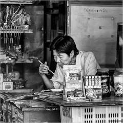 Lunchtime (John Riper) Tags: johnriper street photography straatfotografie square vierkant bw black white zwartwit mono monochrome chiangmai thailand streetfood candid john riper xt2 fujifilm xf18135 woman eating lunch chop sticks pasta pad thai shop taiyo